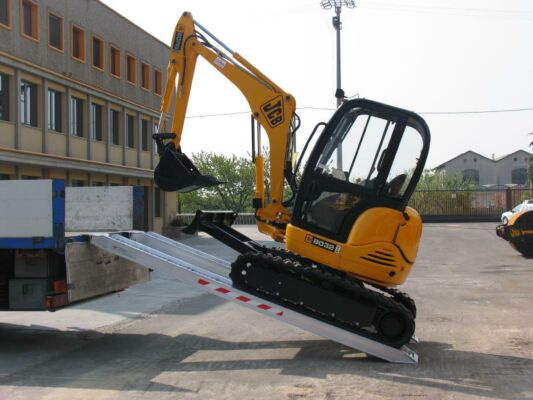 Mini digger driving up loading ramps