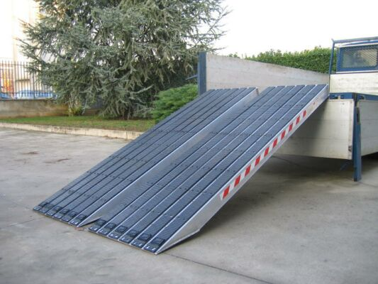 Rubber coated ramps resting on tipper truck