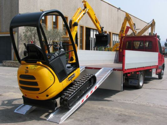 Mini digger on aluminium loading ramps