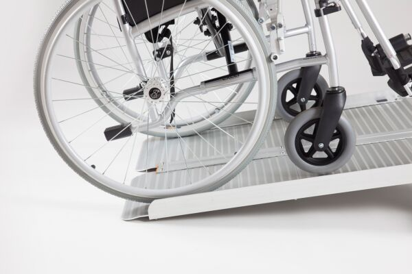 Manual wheelchair on folding wheelchair ramp